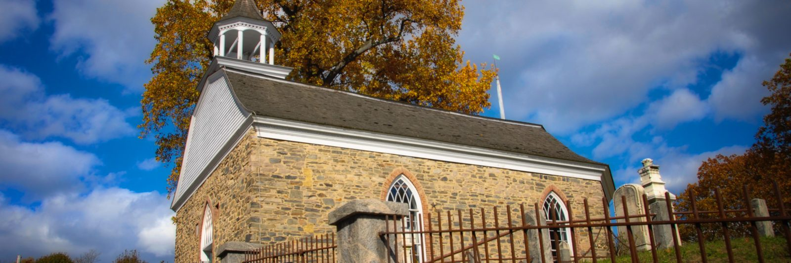 Sleepy Hollow's Old Dutch Church stands against a blue sky and dramatic clouds.
