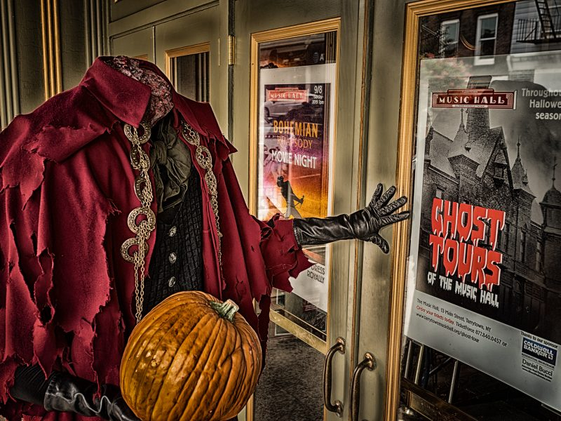 The headless horseman stands outside the Tarrytown Music Hall in front of a poster for the Hall's ghost tours.