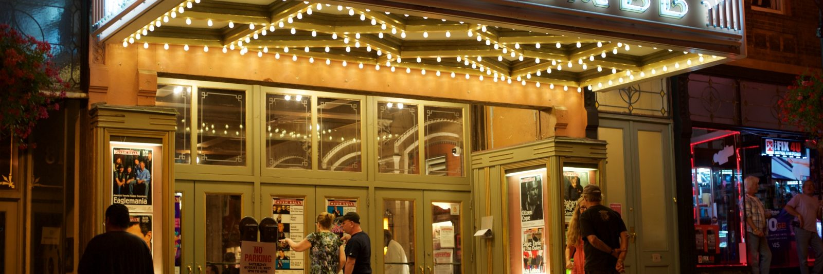 Patrons gather at night under the illuminated marquee of Tarrytown Music Hall.