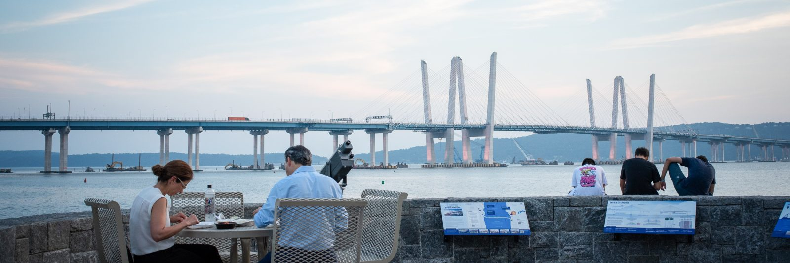 A couple seated at the observation deck at Pierson Park in Tarrytown, New York, with Mario Cuomo Bridge in background.