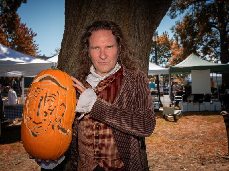 Storyteller Jonathan Kruk holds a carved jack-o'-lantern at a farmers market.