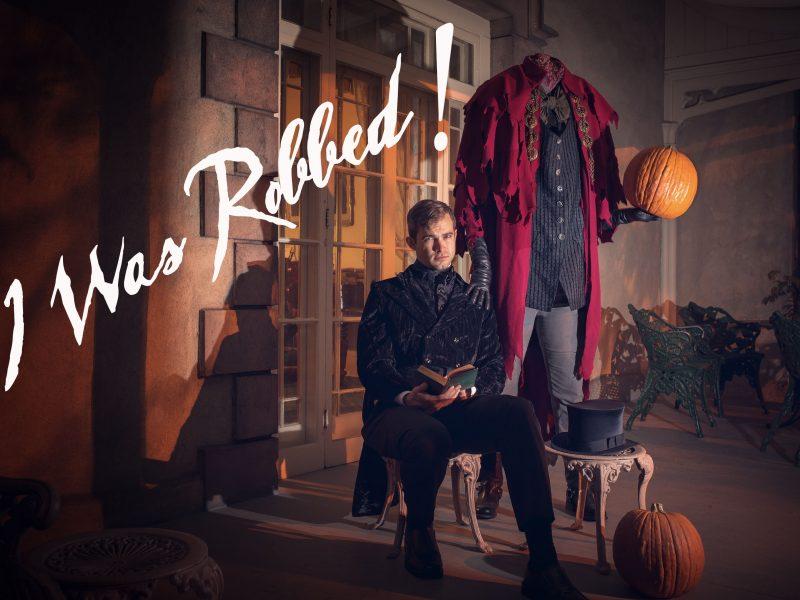 The headless horseman stands beside a seated Washington Irving on the verandah of Sunnyside.