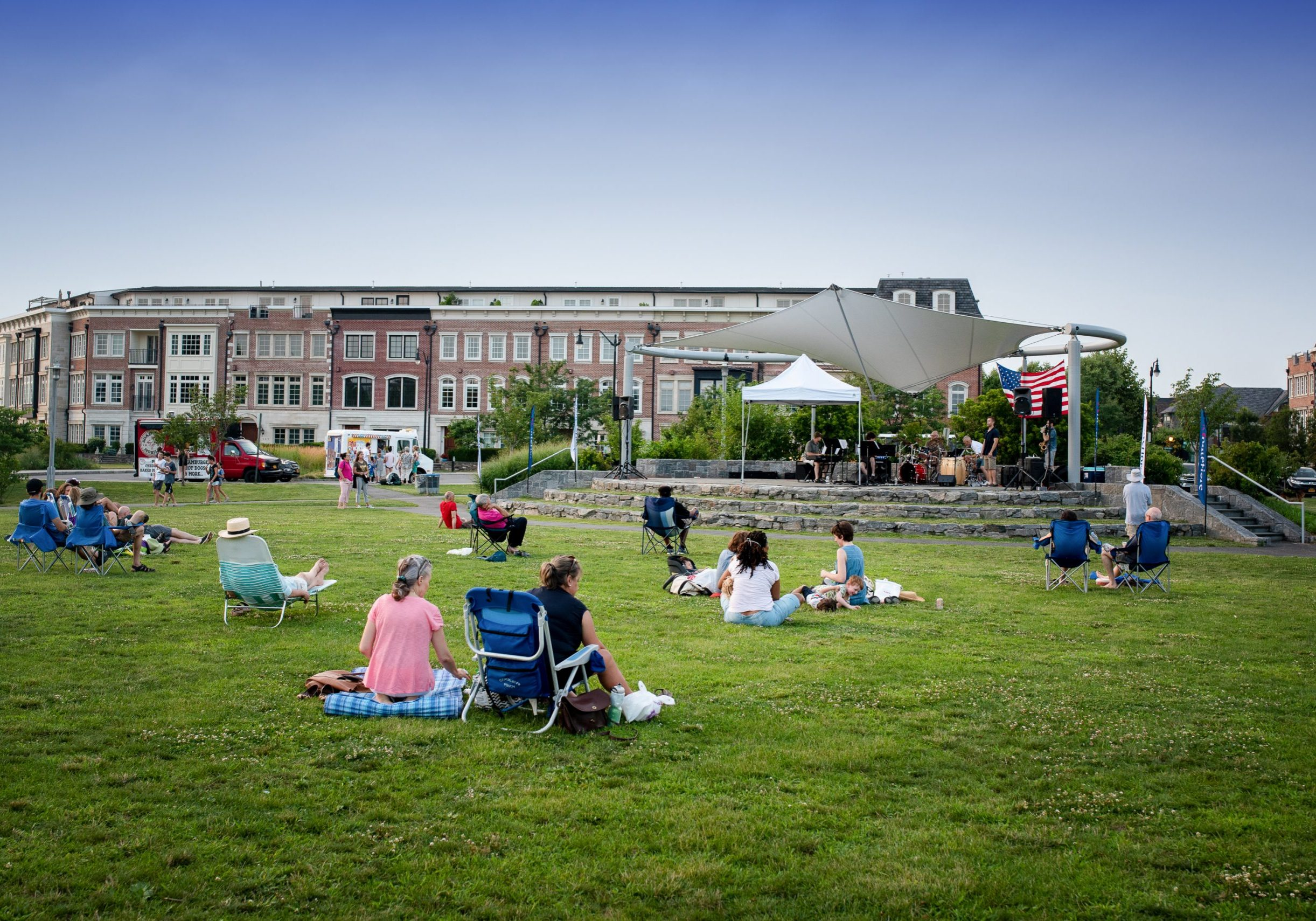 Audience seated on the lawn at Pierson Park in Tarrytown, New York, listening to jazz concert.